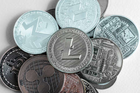 litecoin coin dominates the background of multicolored coins of different cryptocurrencies close up on a light background top view Banco de Imagens