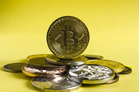 the bitcoin coin dominates the background of multicolored coins of various cryptocurrencies close up on a Golden background