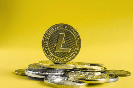 litecoin coin dominates the background of multicolored coins of various cryptocurrencies close up on a gold background