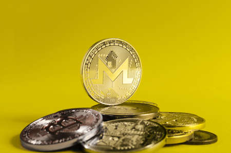 monero coin dominates the background of multicolored coins of various cryptocurrencies close up on a light background