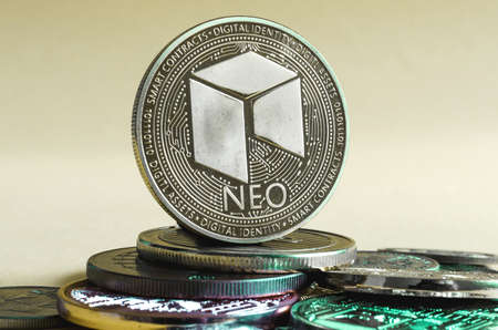 neo coin dominates the background of multicolored coins of different cryptocurrencies close up on a light background