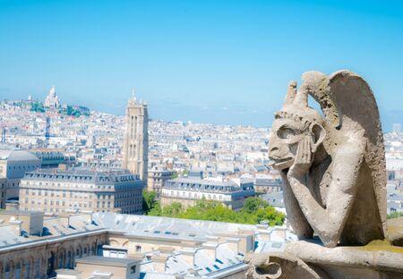 chimera: Gargoyle (chimera) on Notre Dame de Paris close up overlooking blur city at a summer day