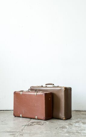 overfilled: Vintage leather suitcase on white wall.