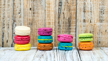 confections: Colorful macarons on vintage pastel background. Macaron is sweet meringue-based confection.