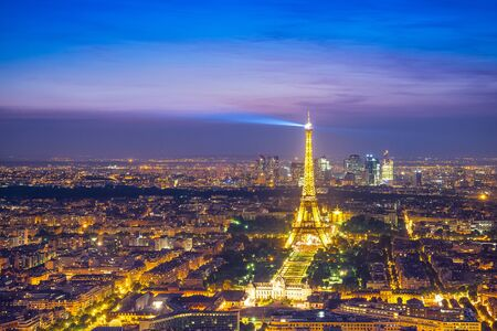 newsworthy: Paris - Jun 19: Aerial view of Eiffel Tower Light and Beam Performance Show at Dusk on Jun 19, 2014. Eiffel Tower is the highest monument in France use 20,000 light bulbs in the show. Editorial