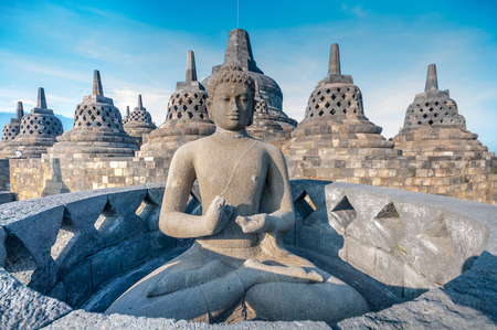 Ancient Buddha statue and stupa at Borobudur temple in Yogyakarta, Java, Indonesia.