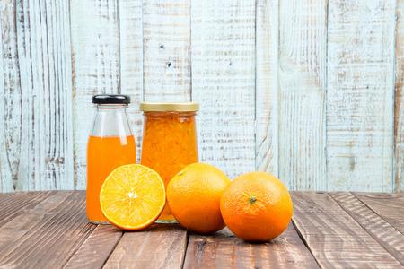 Fresh orange and juice on vintage wooden table background