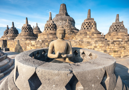 statue: Ancient Buddha statue and stupa at Borobudur temple in Yogyakarta, Java, Indonesia.