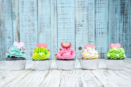 assortment: Colorful Cupcake on wood vintage background