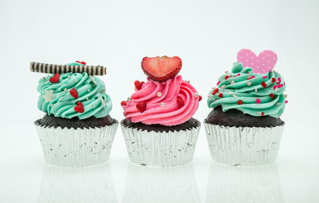 vanilla cupcake: colorful cupcakes with beautiful decoration over white background