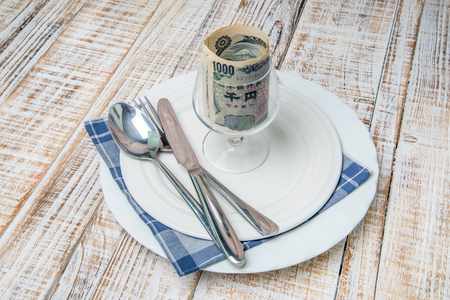yen note: Wallet and Japan yen bank note money in plate on the wooden table background Stock Photo