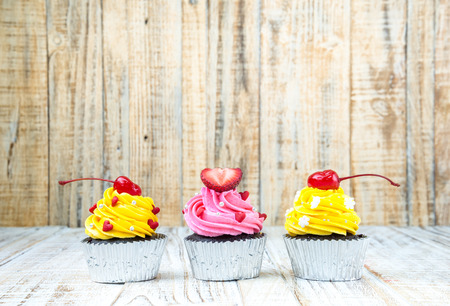 cupcakes: Colorful Cupcake on wood vintage background