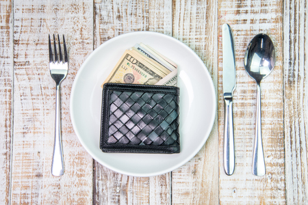 batch of dollars: Wallet and US Dollar bank note money in plate on the wooden table background