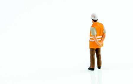 obrero trabajando: Miniatura trabajador de la construcción las personas concepto ingeniero en el fondo blanco con un espacio para el texto Foto de archivo