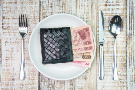over paying: Wallet and china Yuan bank note money in plate on the wooden table background