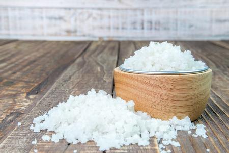 Sól w filiżance na drewnianym tle.