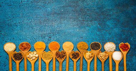 ESPECIAS: Variedad de especias y hierbas en una cuchara de un fondo de madera.