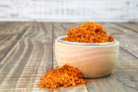 safflower: safflower dried in a cup on a wooden background. Stock Photo