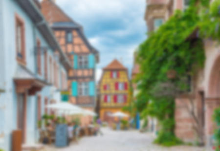 riesling: Abstract blur background of Alley in medieval Riquewihr town on wine route Alsace. Riquewihr known for the Riesling and other great wines produced in the village. Stock Photo