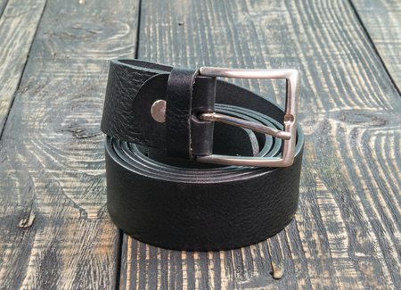 whitespace: Black belt on a Wood background Stock Photo