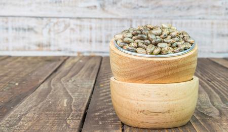 purgative: Castor oil seeds - ricinus communis on wood vintage background Stock Photo