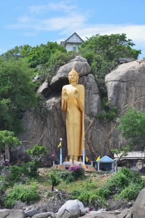 veneration: The Very large standing buddha situated in the Khao Takiab region of Hua Hin in Thailand.