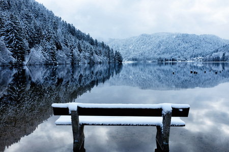 Bench by the Longemer Lake in the Vosges mountains, Xonrupt-Longemer, Lorraine, France. Winter landscape with white snowy trees reflected in water. Standard-Bild