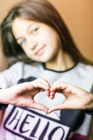 girl showing hands heart