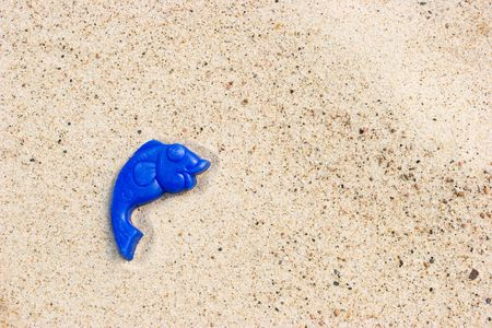 seacoast: Lost toy fish on a sandy beach Stock Photo