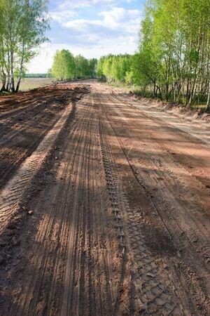 grader: Dirt road with  grader tracks