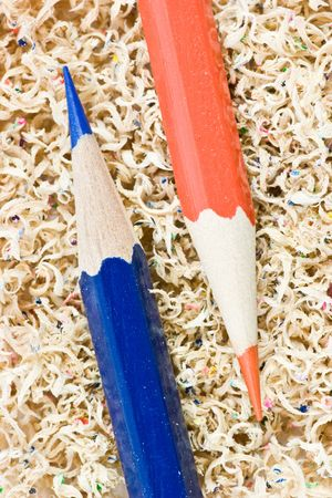 Blue and red wooden pencils in pencil shaving photo