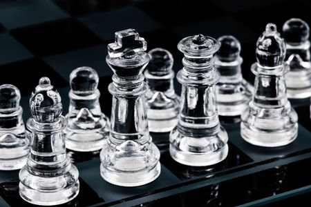Glass chess pieces in start position on glass board photo