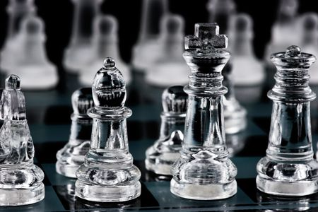 Glass chess pieces on glass board photo