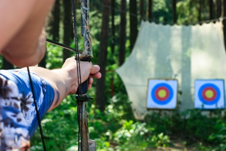 finger on trigger: Man aiming bow at targets in summer forest