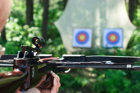 crossbow: Man aiming crossbow at targets in summer forest