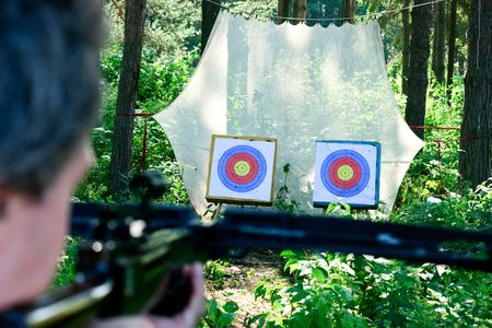 finger on trigger: Man aiming crossbow at targets in summer forest