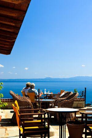 Un uomo anziano e una donna in open-air cafe greco si affaccia sul mare del Golfo Archivio Fotografico