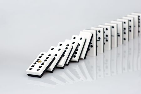 chain reaction: Dominos falling down in chain reaction Stock Photo