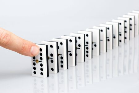 chain reaction: Finger ready to start domino chain reaction