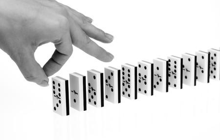 chain reaction: Hand ready to start domino chain reaction, black&white shot Stock Photo