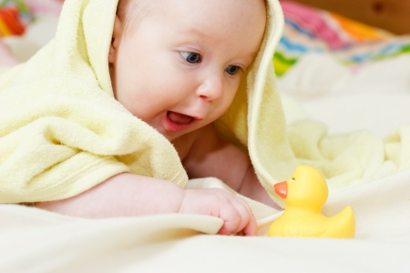 baby facial expressions: Four month baby girl playing with rubber duck Stock Photo
