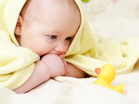 Four month baby girl playing with rubber duck photo