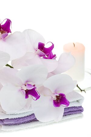 Spa set with white orchid, towels and burning candle on white background photo