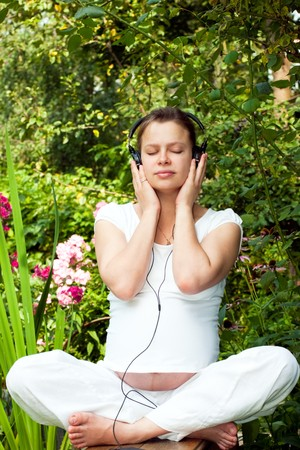 music therapy: Young woman listening to a music at summer garden Stock Photo