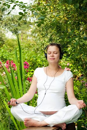 music therapy: Young pregnant woman relaxing at summer garden