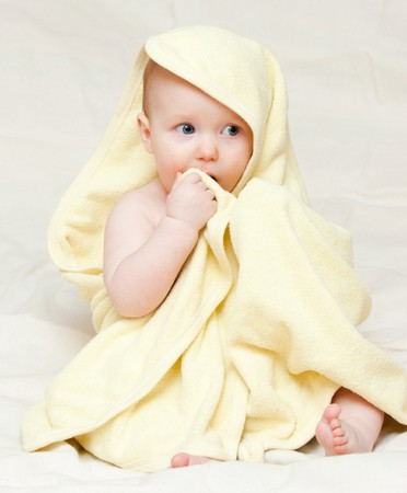 Eight month baby girl wrapped in yellow towel photo