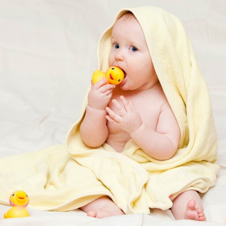 Eight month baby girl playing with rubber duck photo