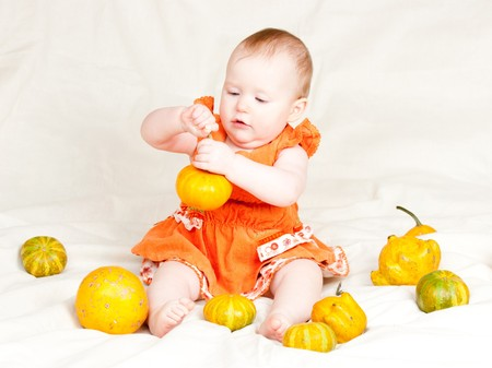 Little baby girl playing with pumpkins Stock Photo - 4301136
