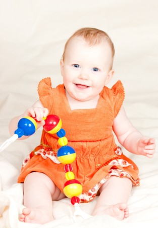 Little baby girl playing with rattle Stock Photo - 4301138