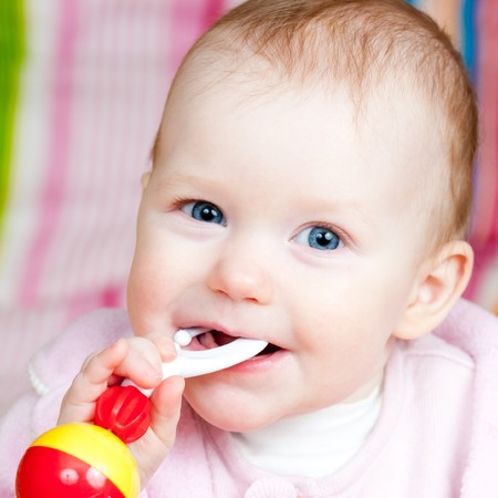 Little baby girl playing with rattle